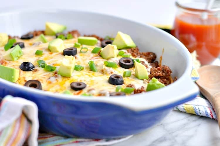 A close up of an enchilada casserole topped with avocado and olives