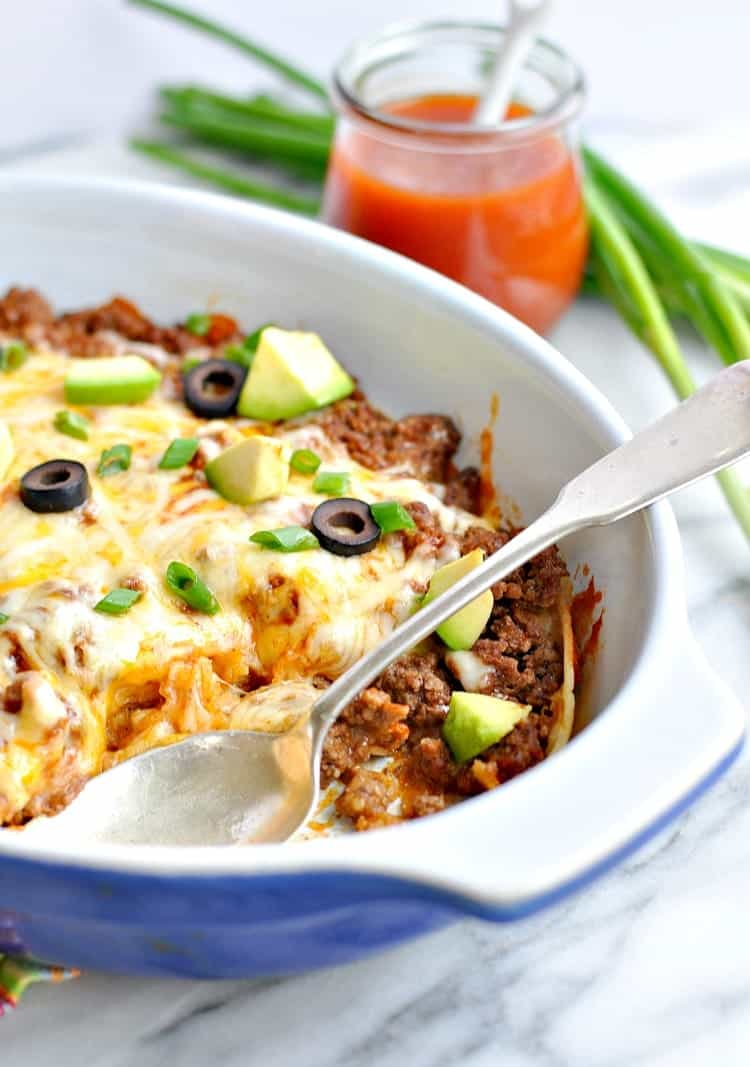 A side shot of an enchilada casserole in a blue dish with a serving spoon