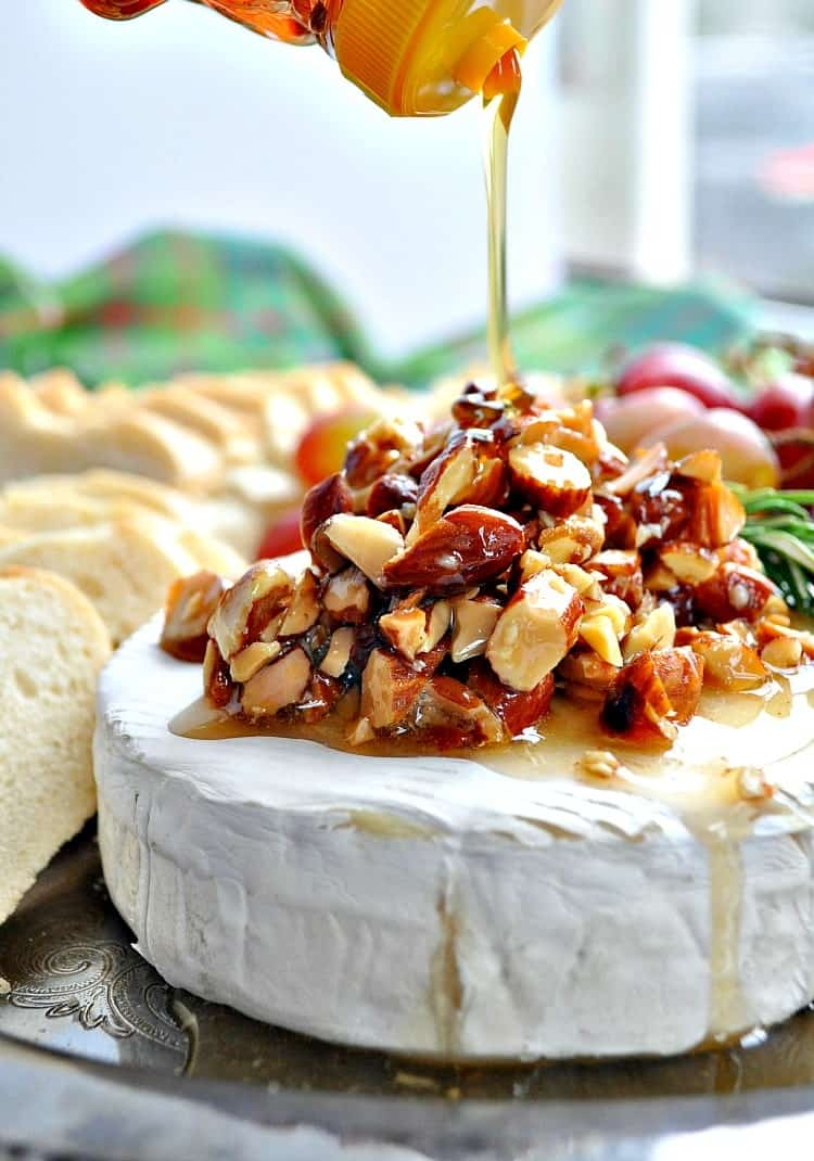 Close up image of drizzling honey over baked brie on a holiday appetizer tray