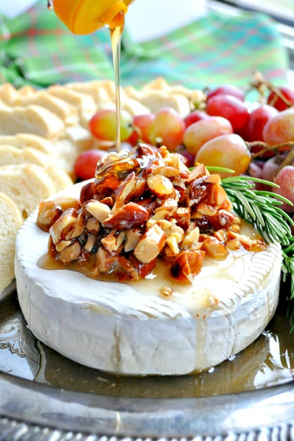 Drizzling honey over a round of baked brie topped with almonds