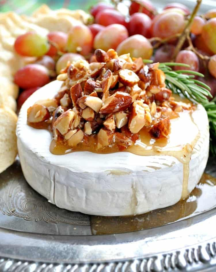 Baked brie recipe with honey and almonds with grapes in the background
