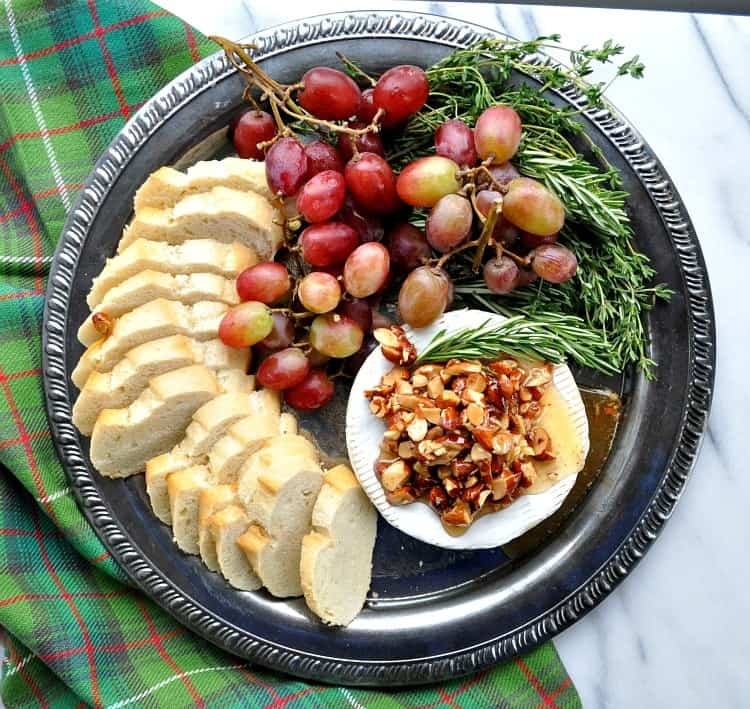 Overhead view of appetizer tray with grapes, baguette, herbs and baked brie