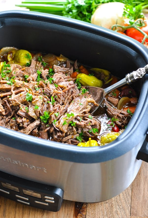 Italian beef roast in the slow cooker with serving spoon