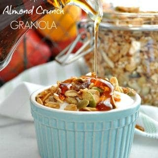 A small blue bowl filled with maple almond granola and maple syrup getting poured over