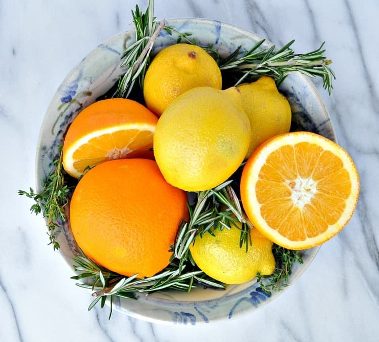 An overhead shot of citrus fruits in a bowl with herbs
