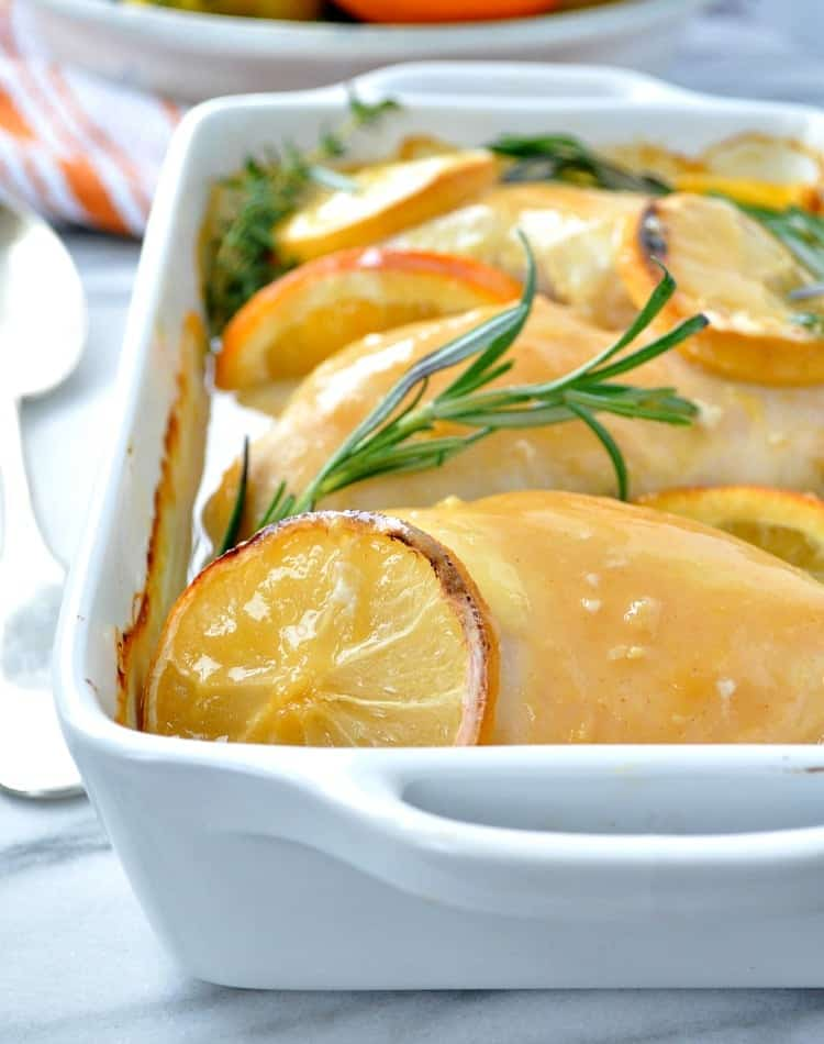 A close up of citrus and herb baked chicken in a white casserole dish
