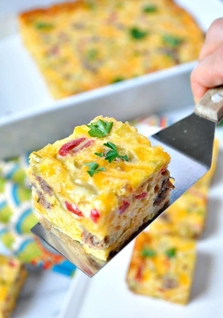 A close up of sausage and cheese squares topped with green herbs