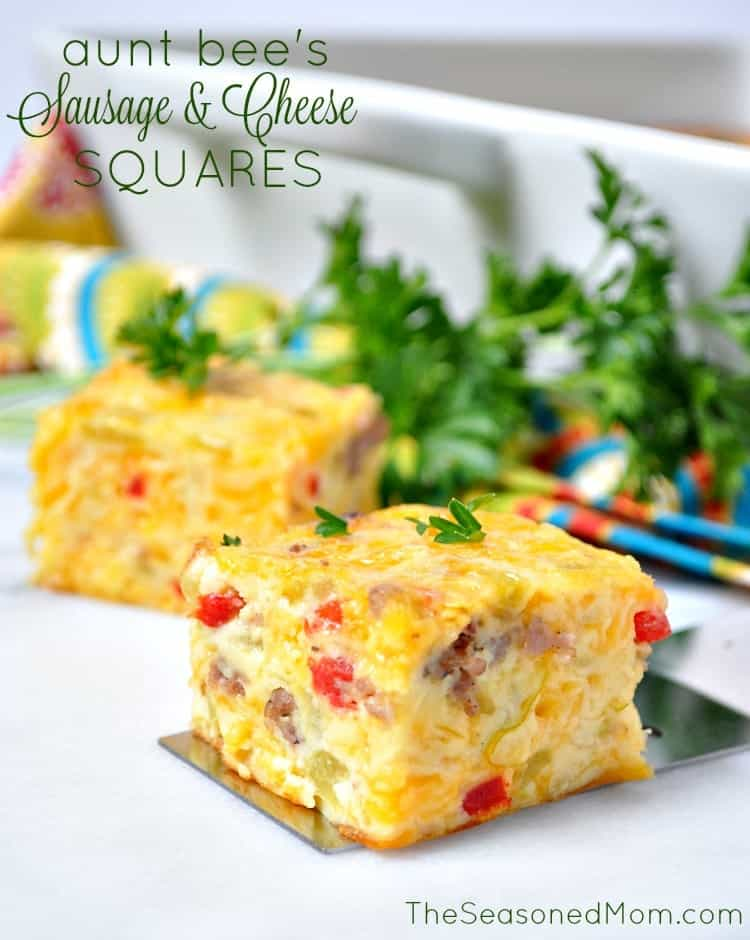 A close up of sausage and cheese squares with green herbs