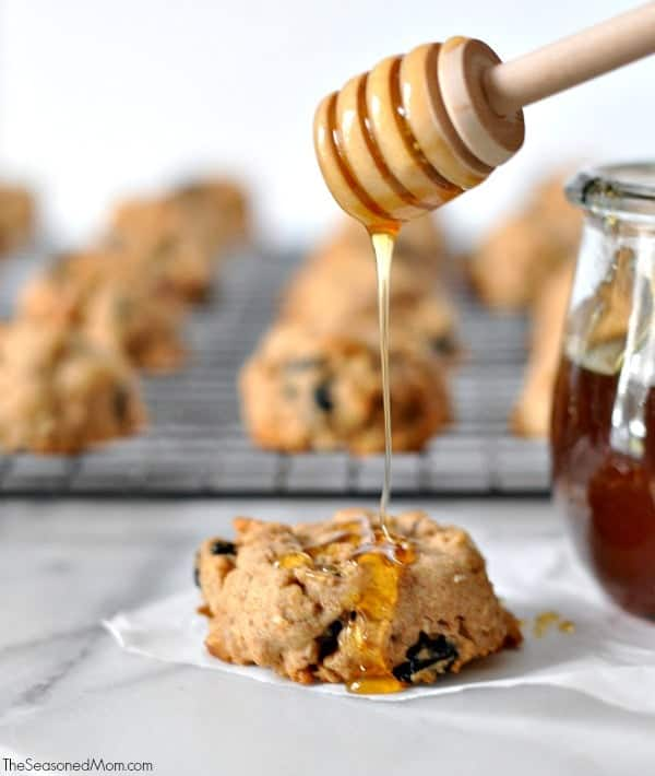 A photo of a healthy trail mix cookie getting drizzled with honey