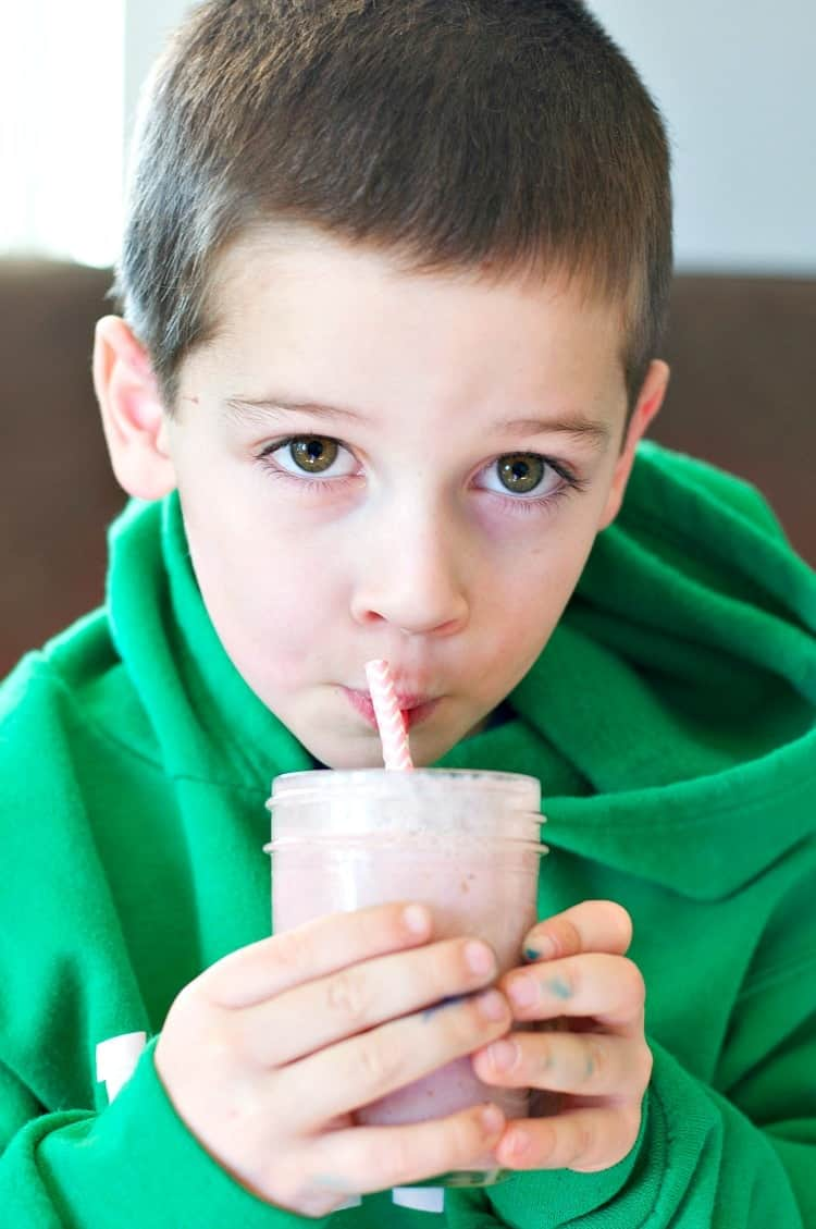 A boy drinking a berry smoothie with a straw