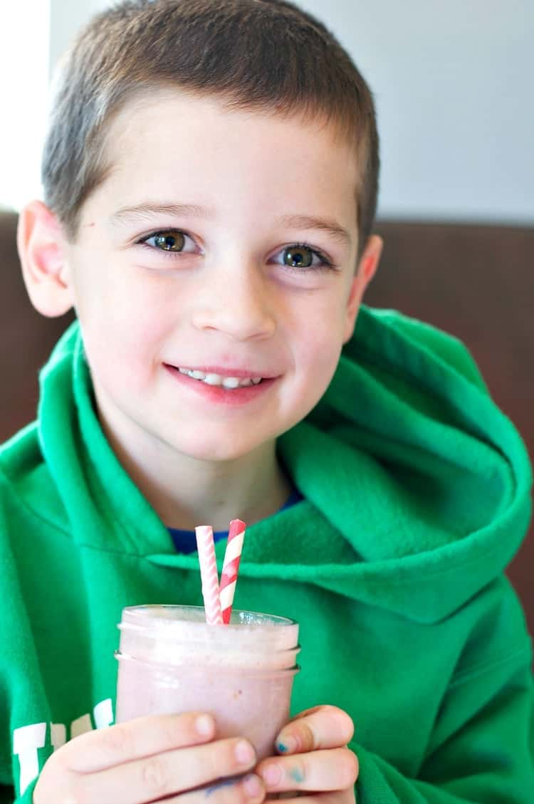 A boy holding a berry smoothie with two straws