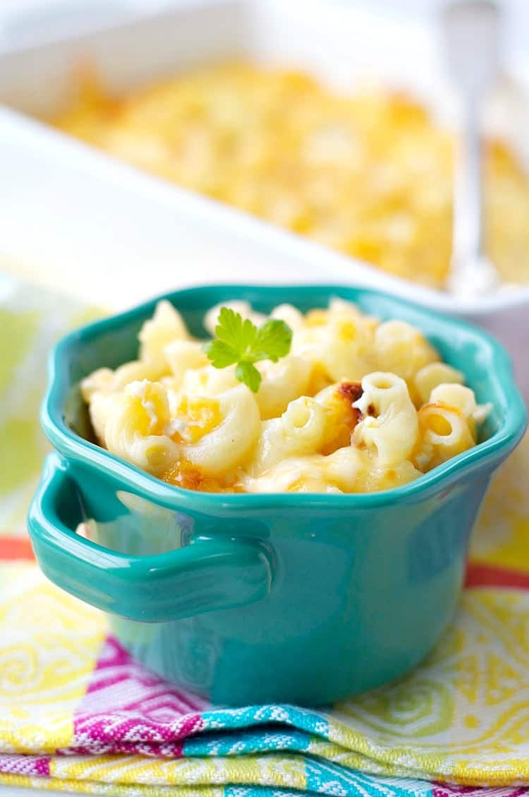 A blue bowl of macaroni and cheese topped with parsley