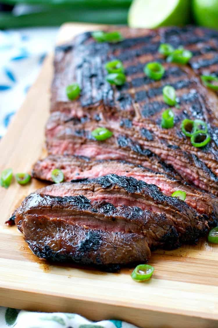 A close up with slices of flank steak on a board