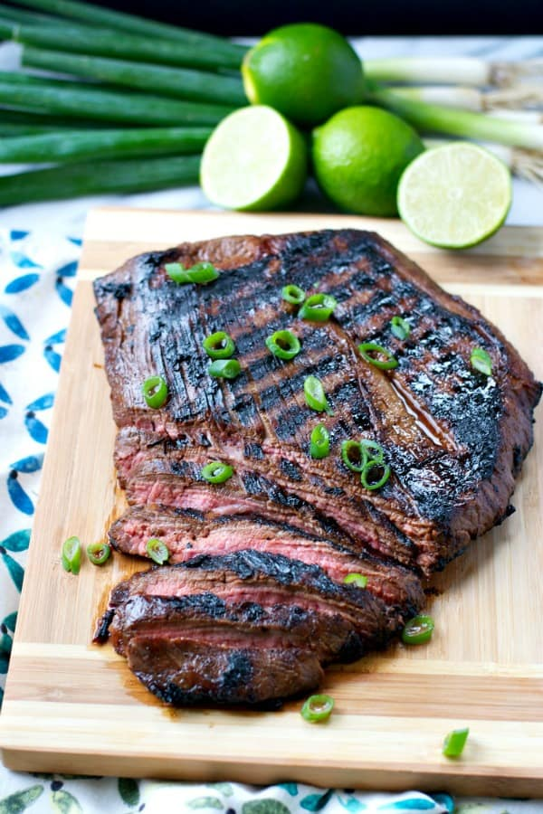 Sliced marinated flank steak on a wooden cutting board