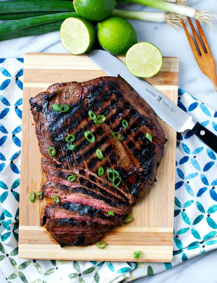 A flank steak on a wooden board with a knife