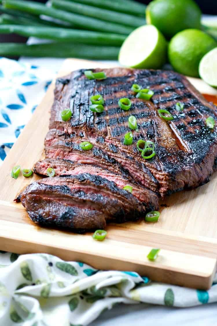 Slices of flank steak on a wooden board garnished with green onions