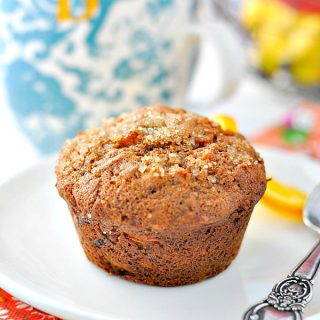 Morning Glory muffin on a white plate with a blue and white mug in the background