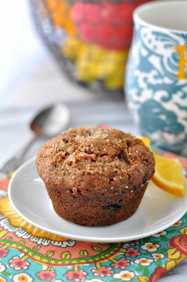 Morning glory muffins on a small white plate with a slice of orange