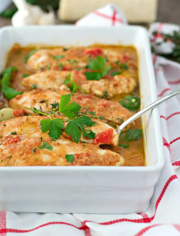 Italian baked chicken in a white casserole dish topped with herbs