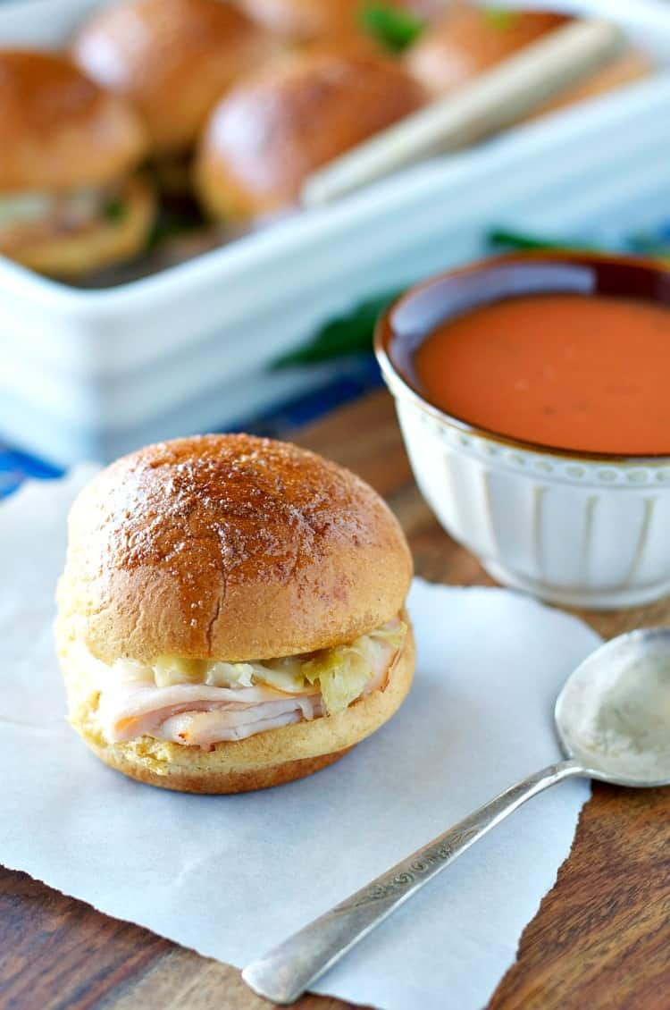 Turkey reuben sliders and a bowl of tomato soup in the background