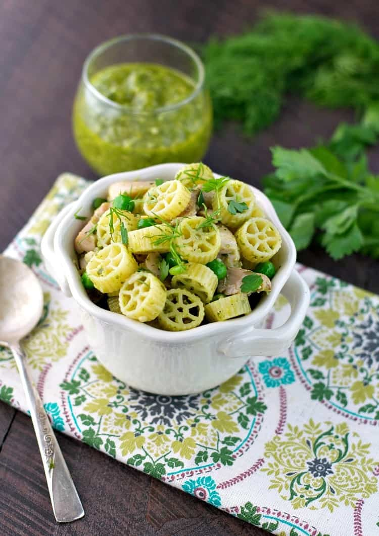 Spring pasta in a white bowl with a jar of pesto at the side