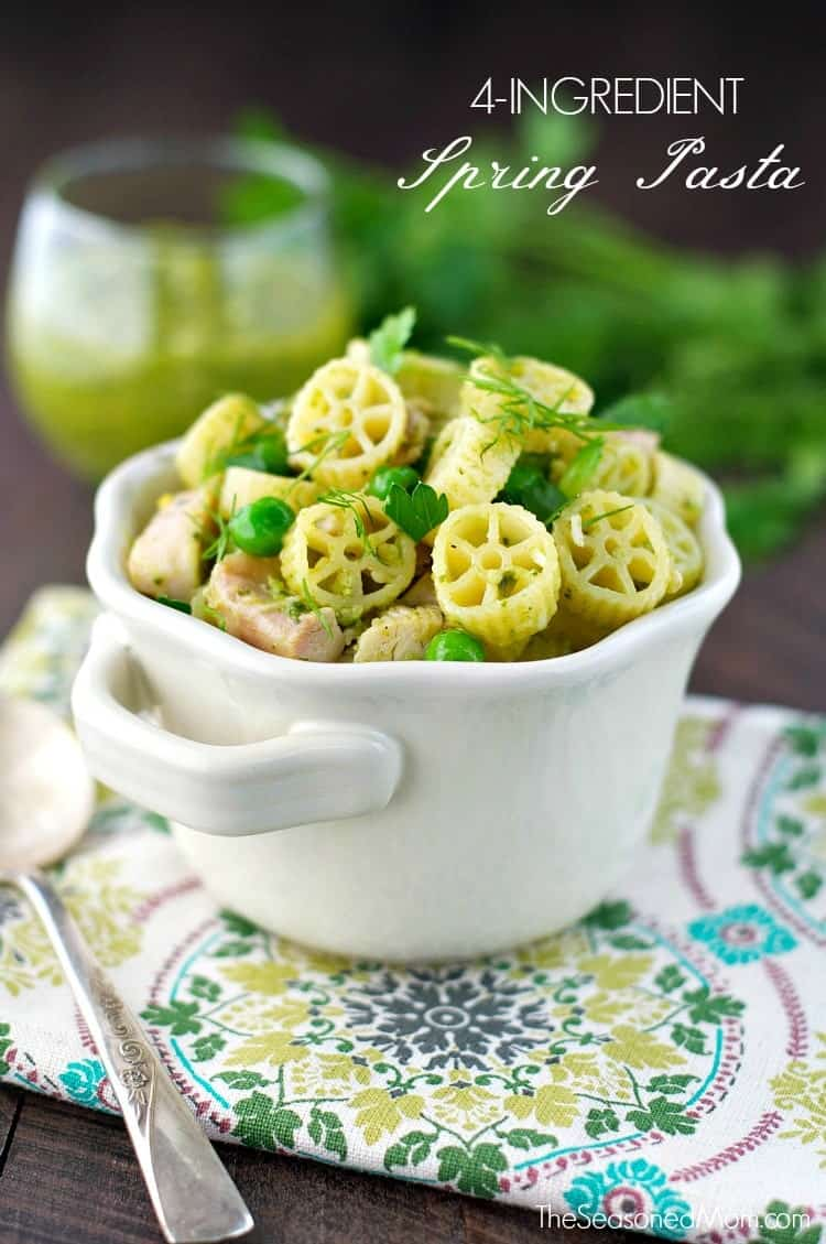 Spring pasta in a small white bowl topped with herbs