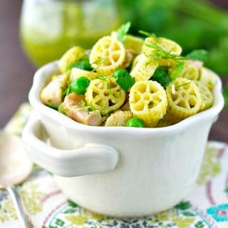 White bowl full of chicken pesto pasta with fresh herbs on top
