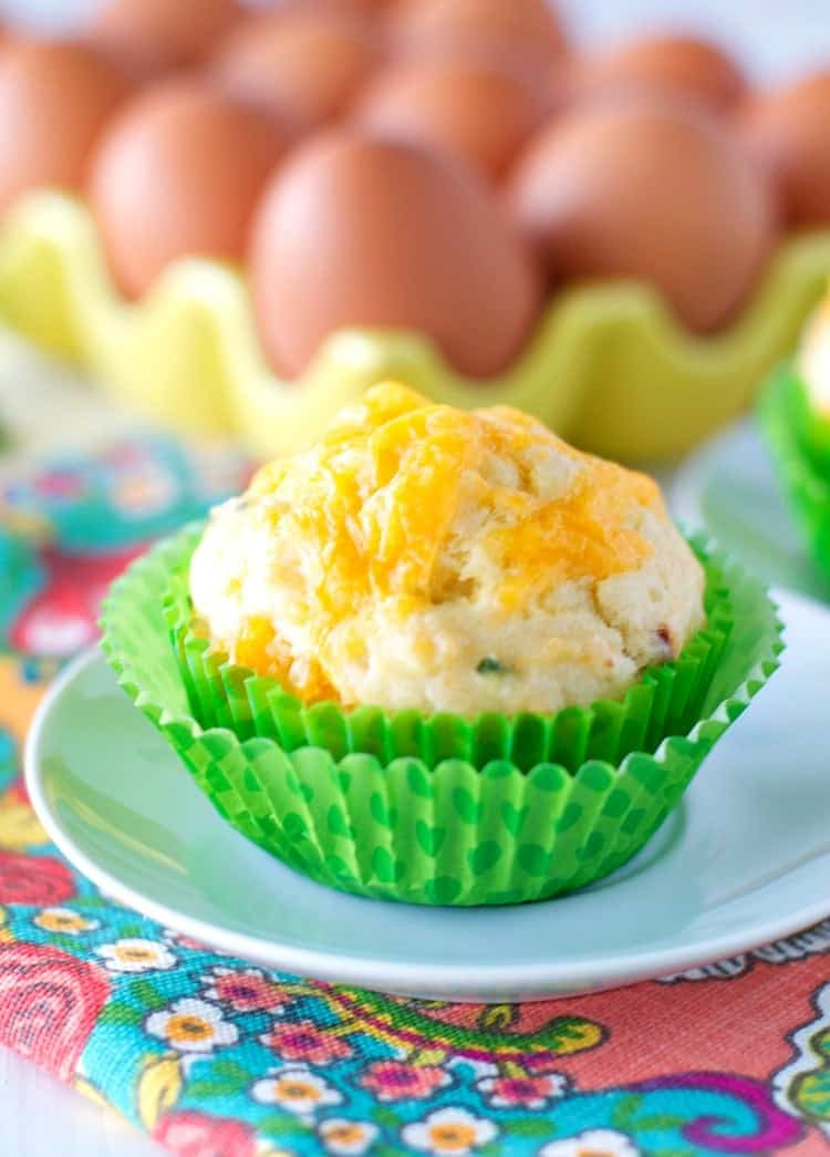 A close up of cheese and chive bacon muffin in green muffin cases with eggs in the background