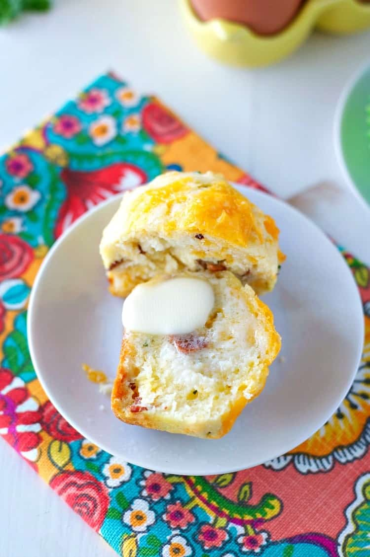 An open cheese and chive bacon muffin spread with butter on a white plate