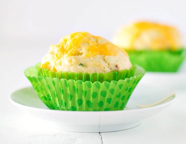 A close up of cheddar and chive bacon muffins in a green case