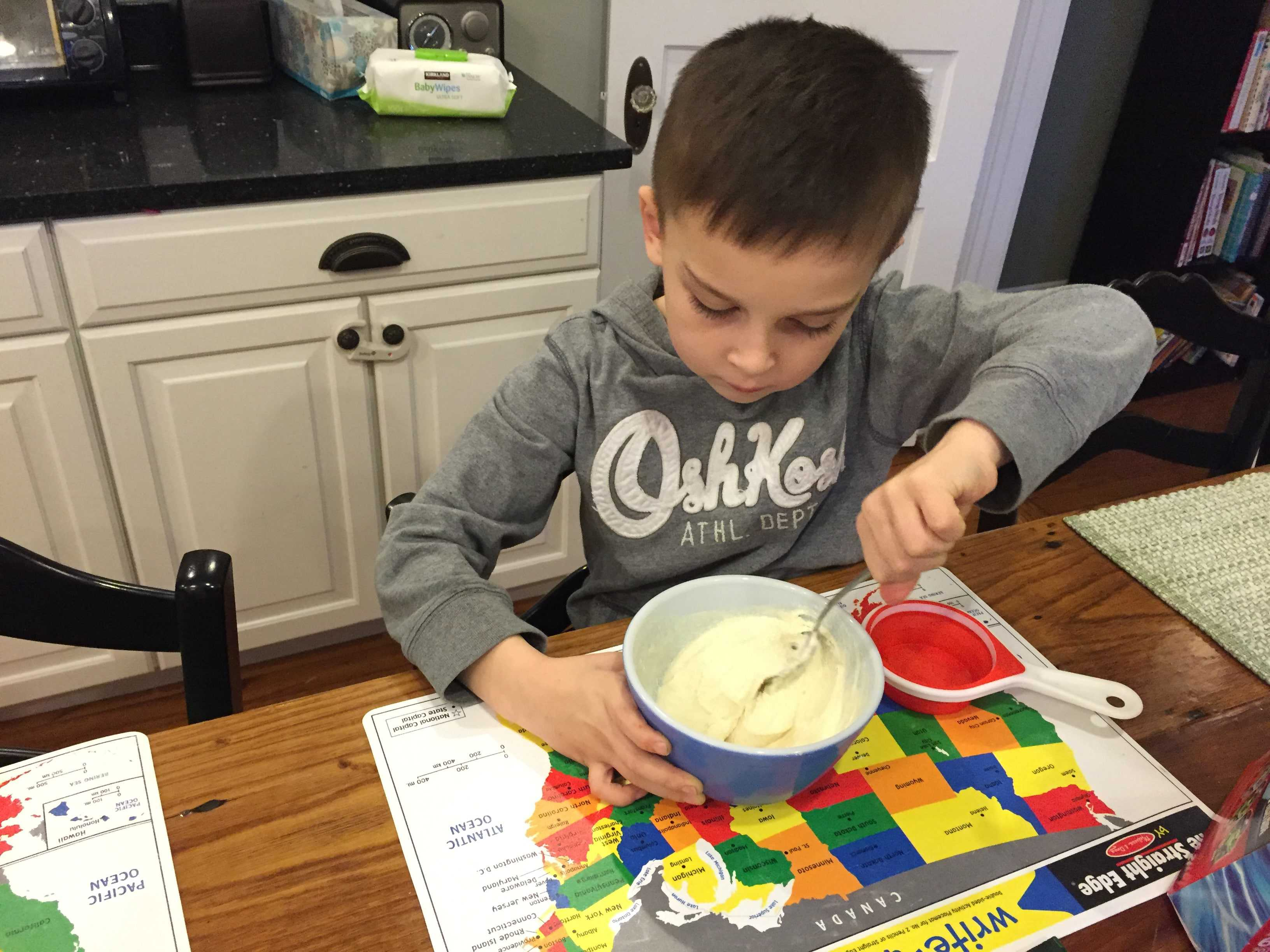 A boy mixing ingredients together to make muddy buddies