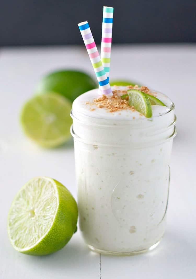 A side shot of a glass of key lime pie smoothie topped with two straws and lime