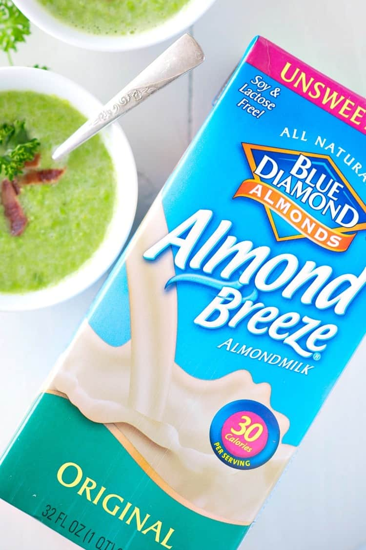 A blue carton of almond breeze almond milk and a bowl of sweet pea soup