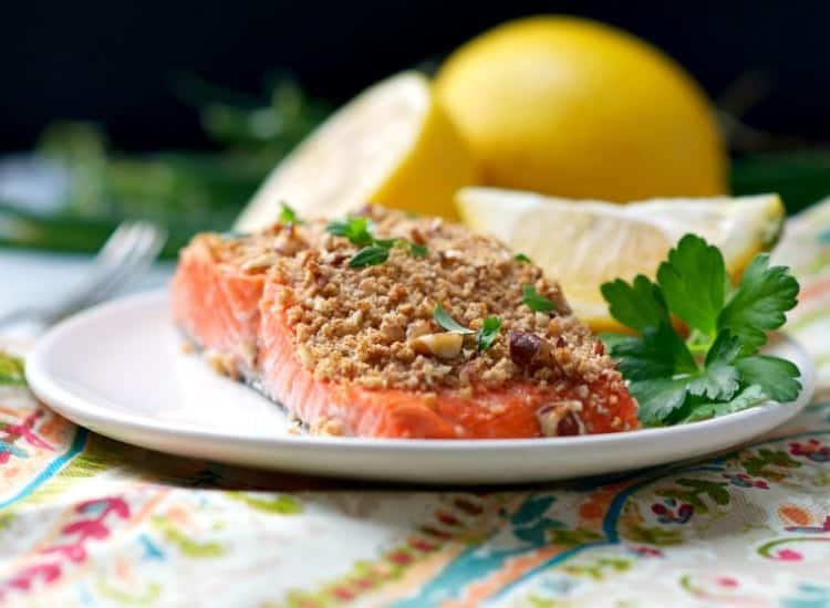 Pecan crusted salmon on a plate with fresh parsley and lemon