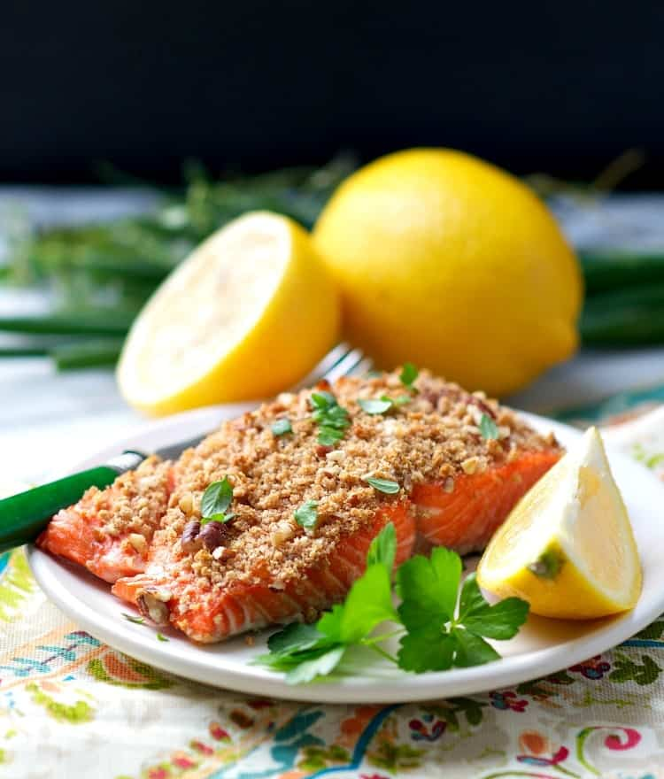 A fillet of pecan crusted salmon on a plate with herbs and lemon