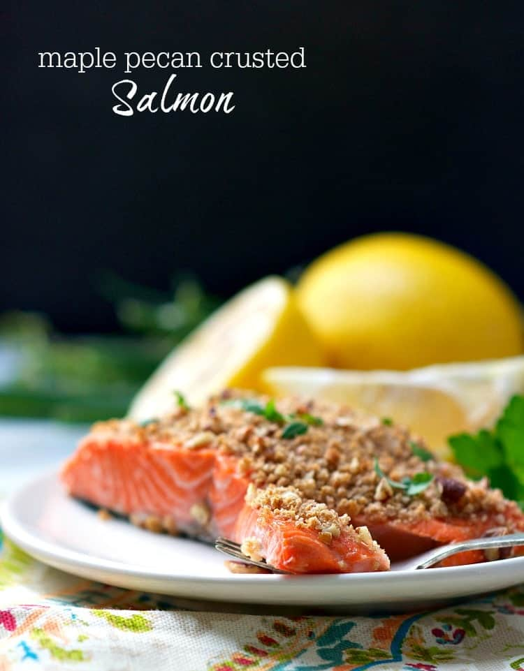Pecan crusted salmon on a plate with lemon wedges