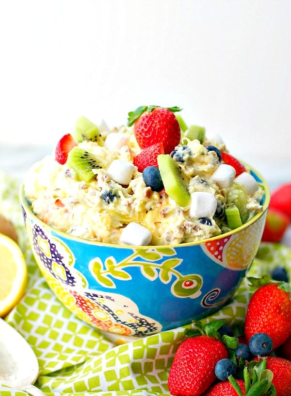 Front shot of a spring fluff fruit salad in a floral bowl with fresh strawberries on top