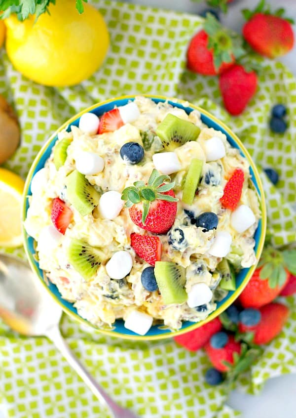 Overhead image of a Spring fluff fruit salad in a bowl surrounded by lemons and fresh berries