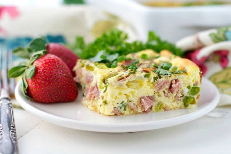 A close up of a baked omelet with eggs and ham on a white plate with strawberries