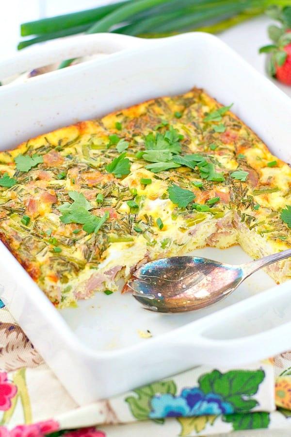 Baked omelet in a white square dish with fresh parsley on top