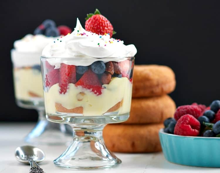 A glass dish filled with a donut trifle and topped with whipped cream and strawberries