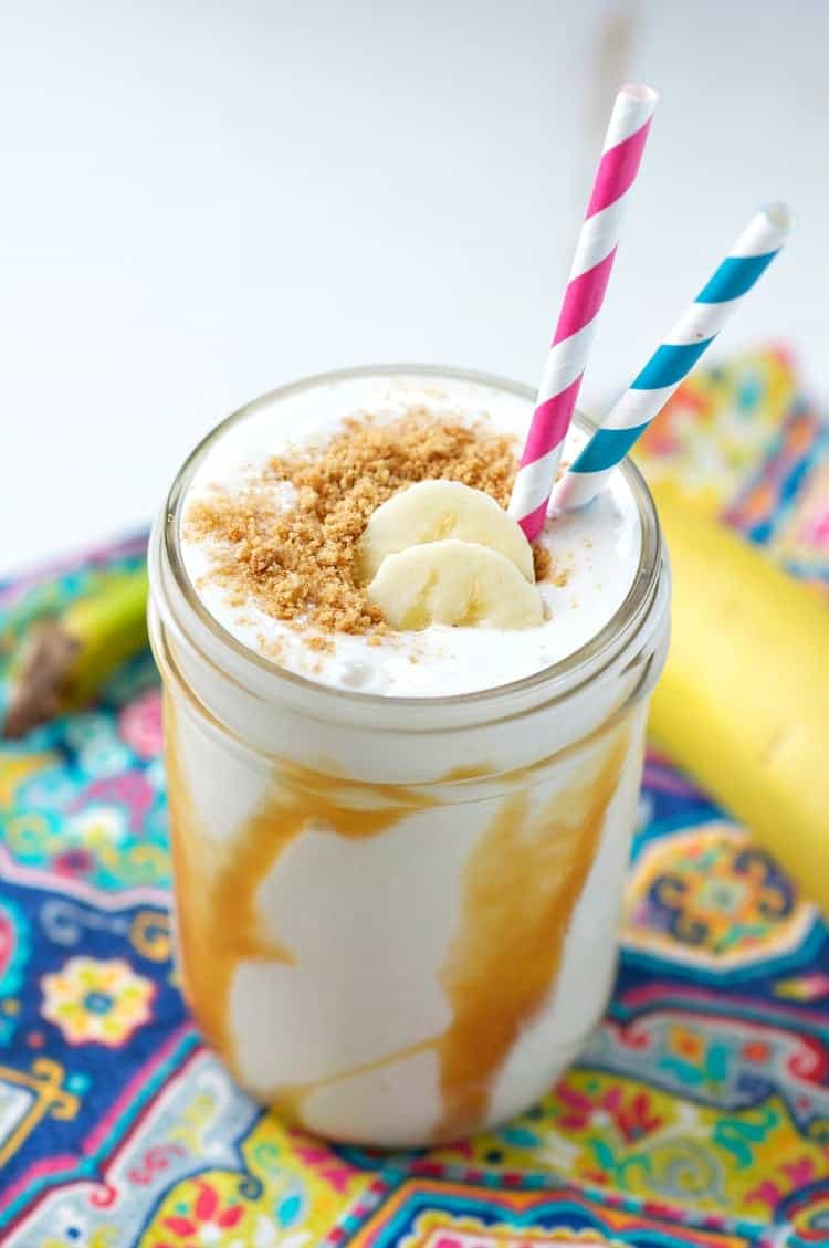An overhead shot of a banoffee pie smoothie with two straws