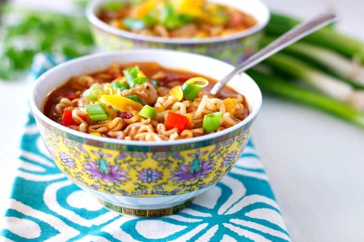 Two ramen noodle bowls topped with green onions