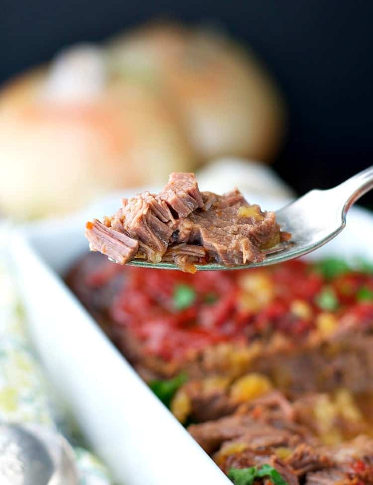 A close up of braised beef brisket on a spoon