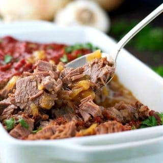 A close up of braised beef brisket in a white casserole dish