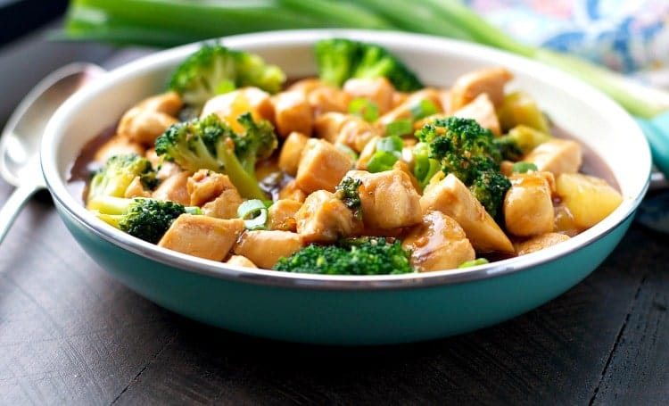 A side shot of chicken teriyaki in a blue bowl with broccoli and sauce