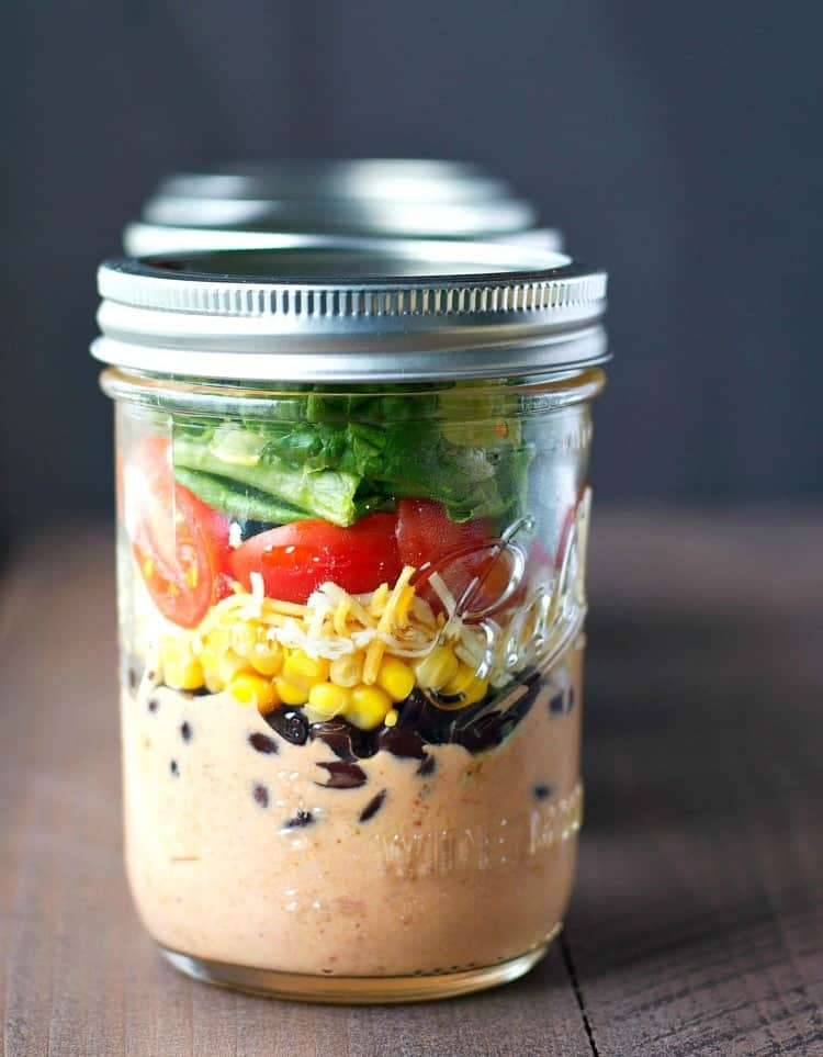 A close up of a chicken taco salad with creamy dressing in a mason jar