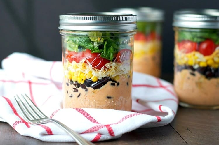 A layered chicken taco salad in a mason jar with a fork at the side