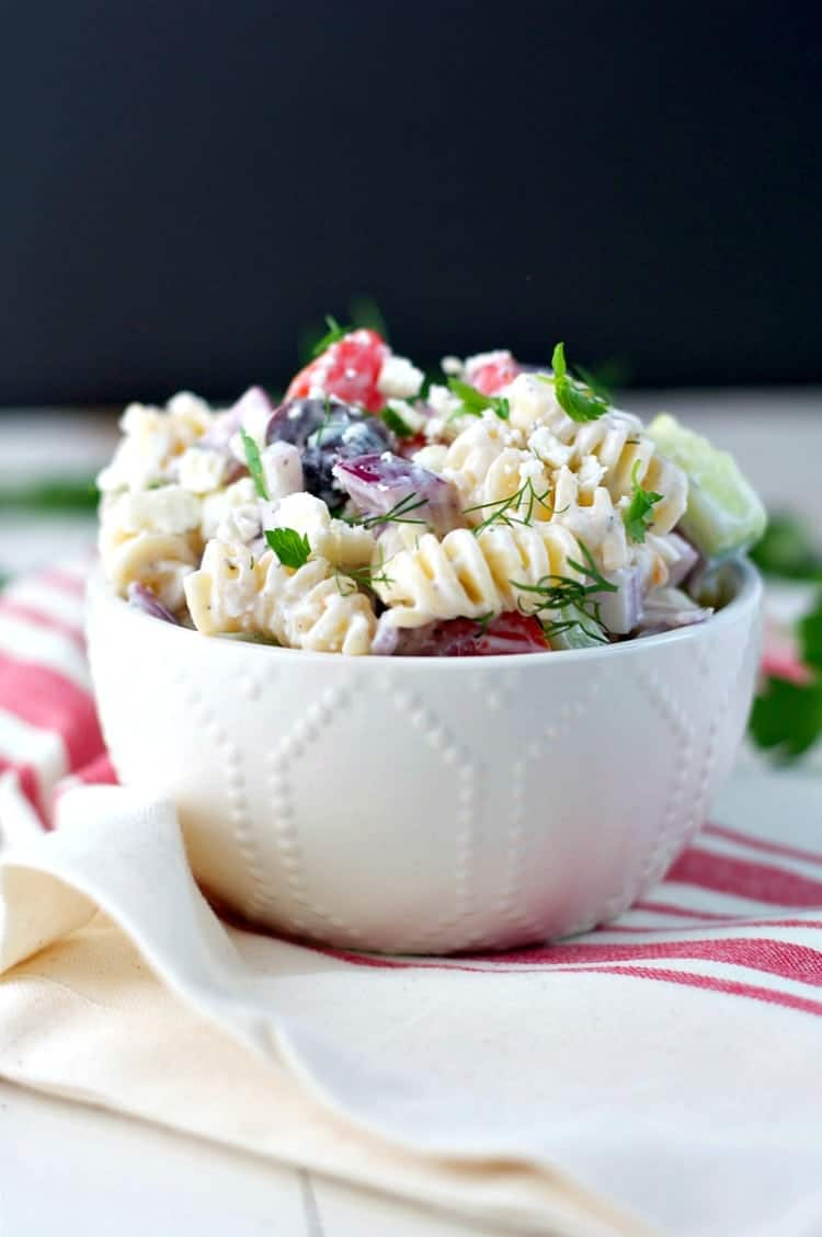 A white bowl of Greek pasta salad sitting on a white and red table cloth