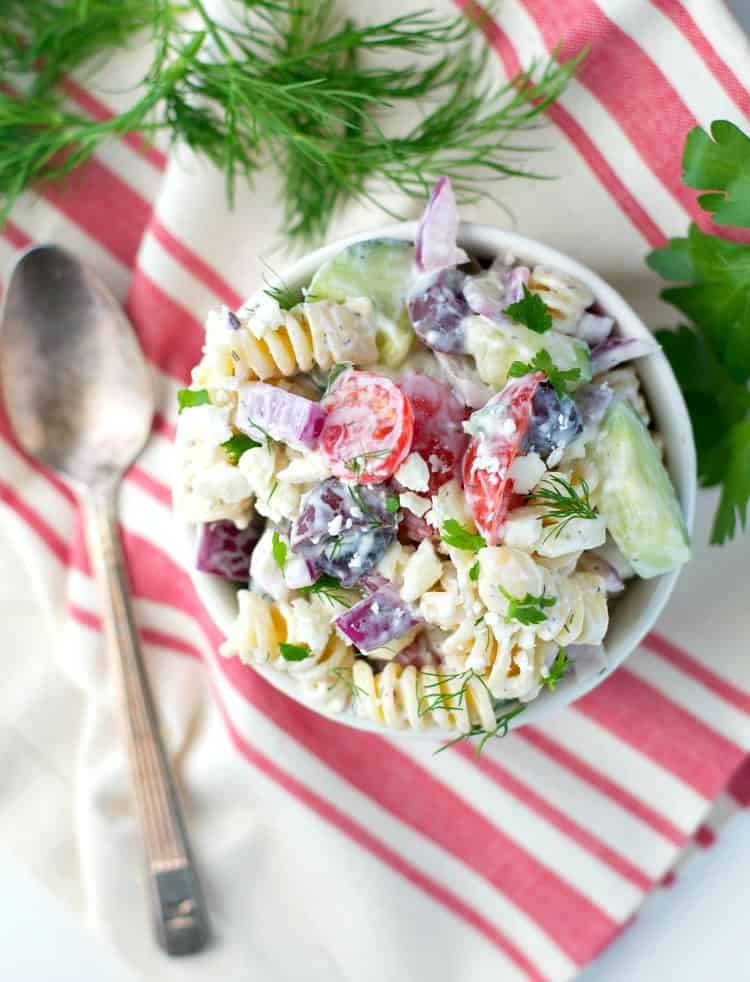 An overhead shot of a Greek pasta salad with tomatoes and cucumber